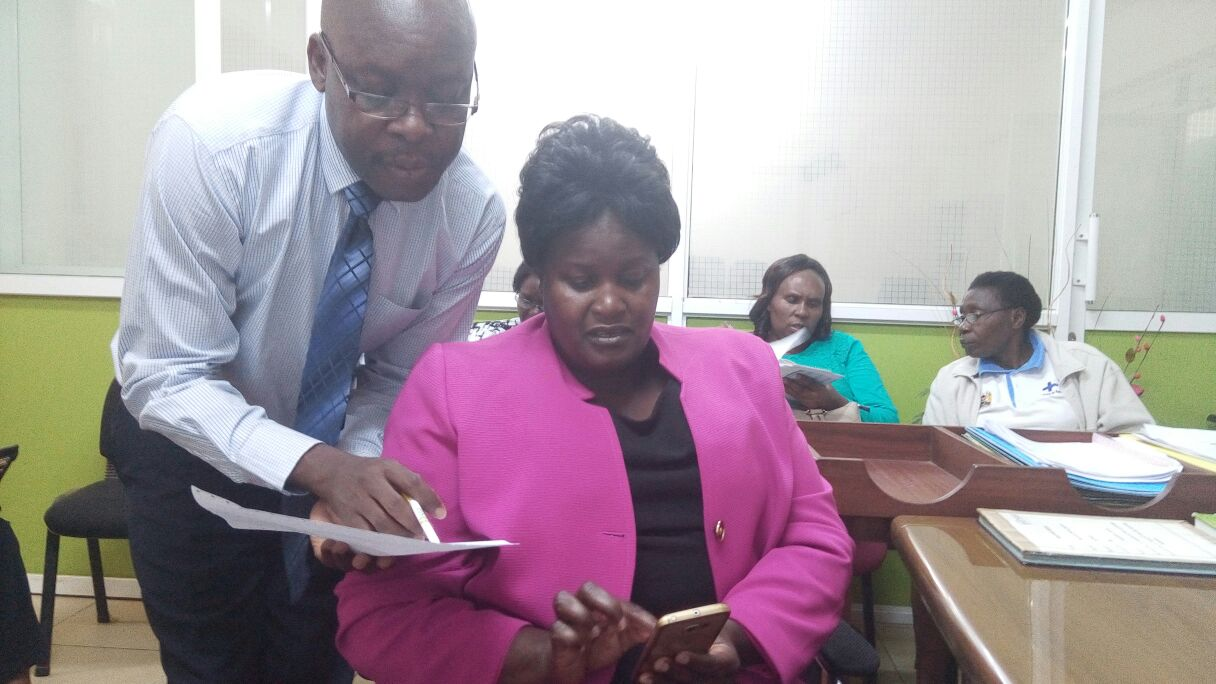 NSSF Kitale Branch Manager Charles Mbeja taking Labour PS Dr Khadija Kassachoon through the NSSF eService