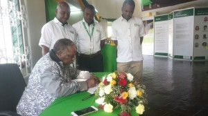 The COTU Secretary General Francis Atwoli and NSSF Board Member signing the visitors book at the ongoing Mombasa ASK Show. Standing by him are Mombasa Branch staff.