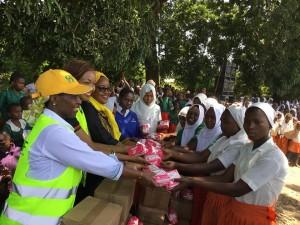 NSSF Trustee Teresia Maina and Ahadi Kenya brand ambassador Cecilia Mwangi donating sanitary towels to the girls in Kilole and Zigira Primary School Ukunda, Kwale County during the jigger clinic.