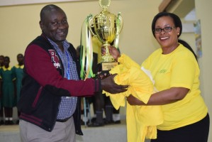 NSSF Vihiga Branch Manager Esther Kemei handing over the trophy to the Head Teacher  Gilwatsi Primary School. The School won in the English Verse category during the Kenya Music Festivals 2019.